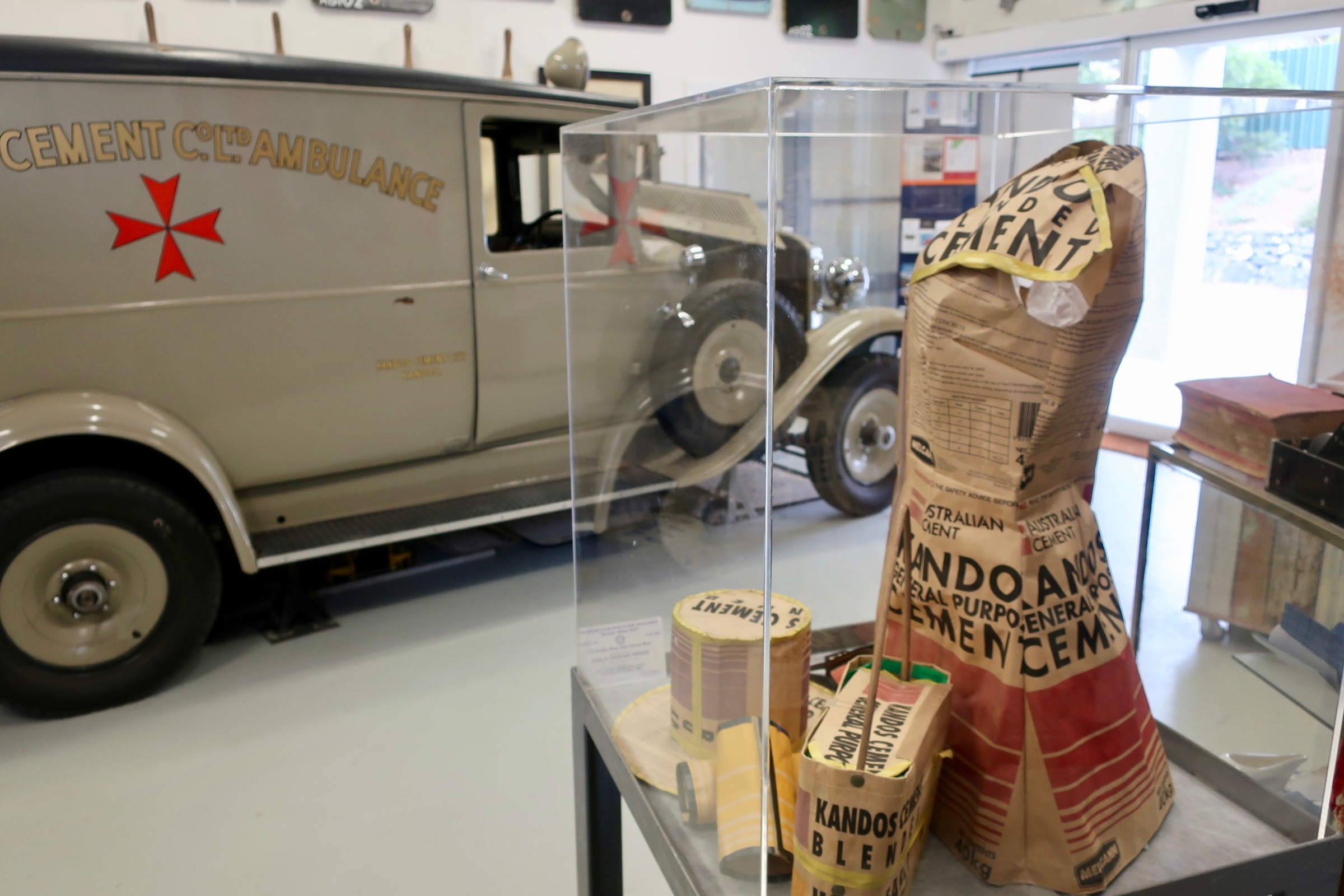 Cement bag dress display with 1930 Nash type 400 ambulance in background