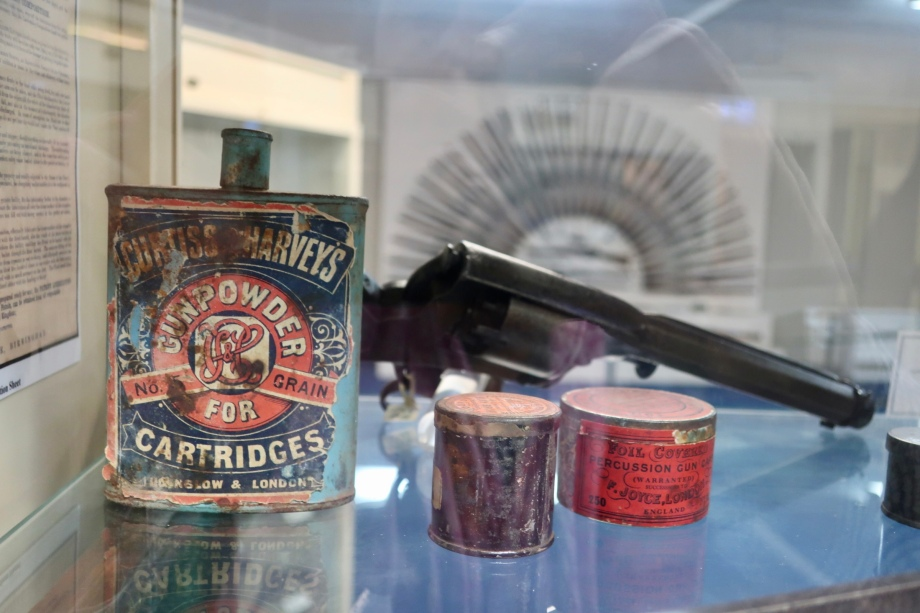 Old tins, gun and the Rising Sun rifle display in the background